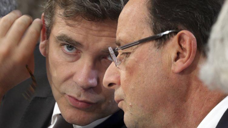 Arnaud Montebourg et François Hollande échangent lors d'une réunion organisée à Cherbourg (Manche), le 30 septembre 2013. (PHILIPPE WOJAZER / AFP)