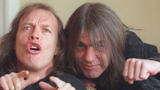 Malcolm Young (à droite) et son frère Angus (à gauche), cofondateurs d'AC/DC, en mars 2000.  (Stan Behal / QMI Agency / AFP)
