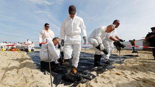 Une opération de dépollution aux hydrocarbures sur la plage de Pampelonne, à Ramatuelle, le jeudi 18 octobre 2018. (DOMINIQUE LERICHE / MAXPPP)