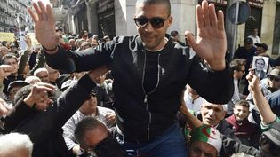 Khaled Drareni porté en triomphe par les manifestants du Hirak dans les rues d'Alger, après avoir été brièvement détenu par la police, puis relâché le 6 mars 2020. (RYAD KRAMDI / AFP)