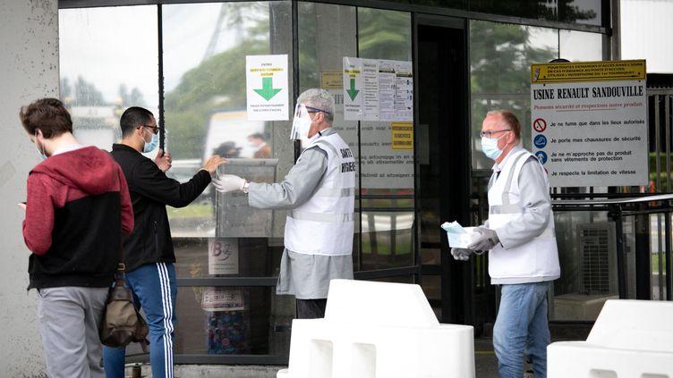 Une distribution de masques sanitaires contre le Covid-19 devant l'usine Renault de Sandouville, en mai 2020. Le site rouvrait alors après la fin du premier confinement. (LOU BENOIST / AFP)
