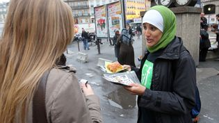 Une bénévole du Collectif contre l'islamophobie en France (CCIF) distribue un pain au chocolat, le 10 octobre 2012 à Paris. (THOMAS SAMSON / AFP)