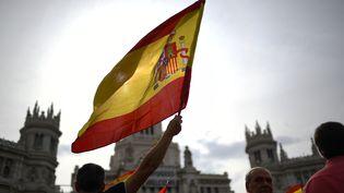 Un homme brandit un drapeau espagnol lors d'une manifestation contre le référendum d'autodétermination en Catalogne, le 30 septembre 2017, à Madrid. (GABRIEL BOUYS / AFP)
