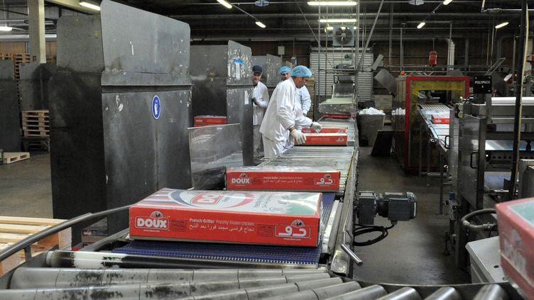 Des employés du volailler Doux travaillent sur une chaîne de l'usine àChâteaulin (Finistère), le 23 janvier 2015. (FRED TANNEAU / AFP)