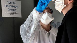 Un prélèvement réalisé au laboratoire CBM69 de Villeurbanne (Rhône), le 23 mars 2020. (JEFF PACHOUD / AFP)
