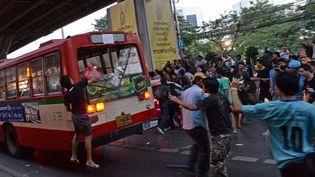 """Bangkok, le 30 novembre 2013, desopposants du gouvernement thaïlandais s'attaquent à des partisans en """"chemises rouges"""" das un bus (CHRISTOPHE ARCHAMBAULT / AFP)"""