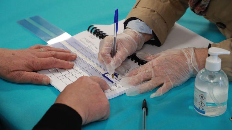 Une électrice portant des gants signe le registre après avoir voté dans un bureau de Cucq (Pas-de-Calais) lors du premier tour des élections municipales, le 15 mars 2020, organisé pendant l'épidémie de coronavirus Covid-19. (LUDOVIC MARIN / AFP)