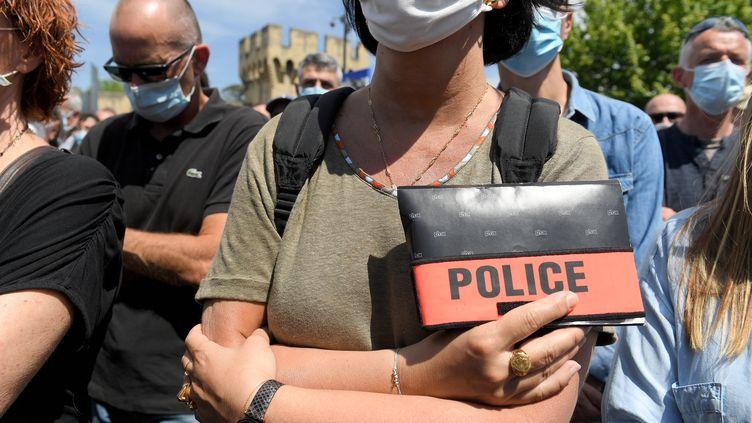 Une policière tient son insigne, lors du rassemblement à Avignon dimanche 9 mai en mémoire d'Eric Masson, cet agent tué lors d'une opération anti-drogue le 5 mai. (NICOLAS TUCAT / AFP)