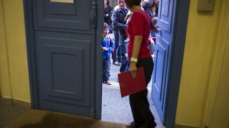 Une professeure attend ses élèves devant la classedans une école parisienne le 4 septembre 2012, (FRED DUFOUR / AFP)