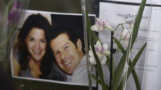 Des fleurs devant la photo de Jessica Schneider et Jean-Baptiste Salvaing, assassinés à leur domicile de Magnanville, dans les Yvelines, le 13 juin 2016. (DOMINIQUE FAGET / AFP)