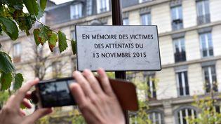 Un homme prend en photo la plaque commémorative en hommage aux victimes des attentats du 13 novembre 2015. (CHRISTOPHE ARCHAMBAULT / AFP)