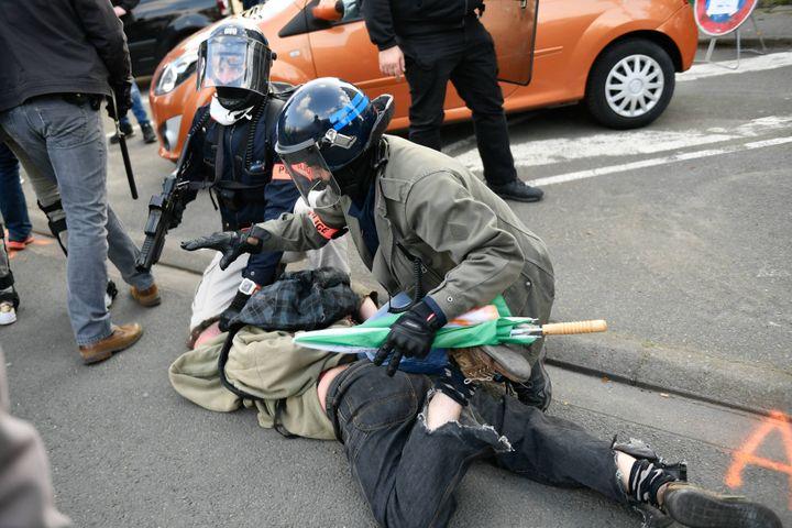 Le policier à droite tient son LBD à la main, et l'arme est cette fois pointée vers le sol devant lui. (MAXPPP)