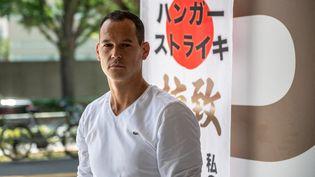 LeFrançais Vincent Fichot, qui a entamé une grève de la faim, devant une gare à Tokyo (Japon), le 10 juillet 2021. (PHILIP FONG / AFP)