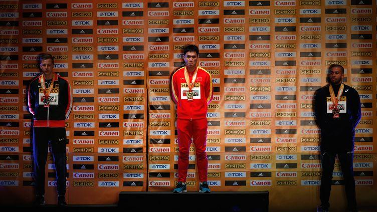 Benjamin Compaoré (à droite) sur le podium des championnats du monde en salle de triple saut derrière le Chinois Dong Bin et l'Allemand Max Hess.  (CHRISTIAN PETERSEN / GETTY IMAGES NORTH AMERICA)