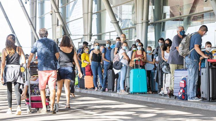 Des voyageurs patientent à l'extérieur de l'aéroport Felix-Eboue à Cayenne, en Guyane, le 10 juillet 2020. (JODY AMIET / AFP)