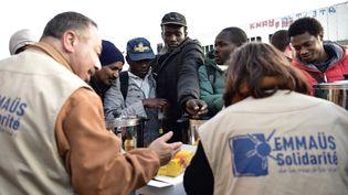 Des membres d'Emmaüs Solidaritédistribuent de la nourriture lors d'une évacuation du campement de la Chapelle, à Paris, le 9 mai 2017. (PHILIPPE LOPEZ / AFP)