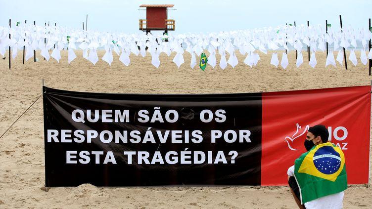 """Une affiche sur laquelle est écrit """"qui est responsable de cette tragédie ?"""", devant des tissus blancs en hommage aux Brésiliens morts du Covid-19, le 8 octobre 2021 à Rio de Janeiro (Brésil). (WILTON JUNIOR / ESTADÃO CONTEÚDO / AFP)"""