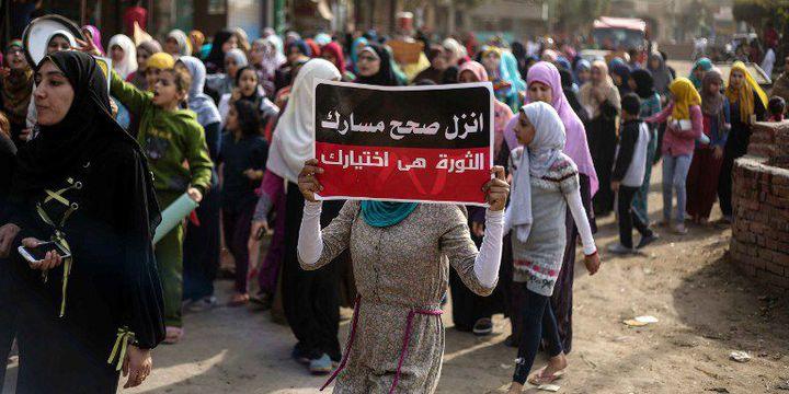 Des manifestants, le 11 novembre 2016, dans un quartier de Gizeh, près du Caire. Ils protestent contre les pénuries et les hausses de prix. «Manifeste pour le changement. La révolution est ton choix», peut-on lire sur la pancarte de la manifestante. (HESHAM FATHY / ANADOLU AGENCY)