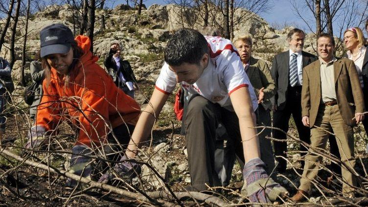 Des jeunes en service civique en plein travail, le 2 avril 2010, à Marseille (Bouches-du-Rhône), lors d'une visite du chantier de restauration du parc des Bruyères en partie dévasté par un incendie en 2009. (ANNE-CHRISTINE POUJOULAT / AFP)