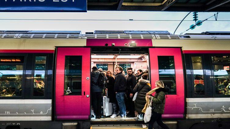 Des passagers montant dans un train de la gare de l'Est, à Paris, le 13 décembre 2019. (MARTIN BUREAU / AFP)