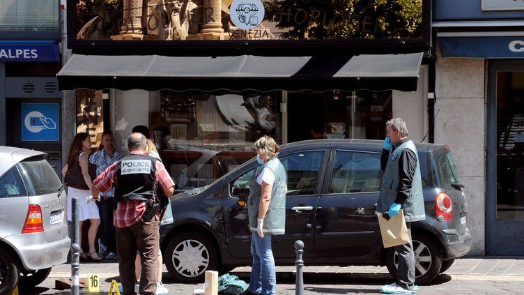 Des policiers enquêtent sur les lieux d'un braquage, vendredi 10 août à Grenoble (Isère). (JEAN-PIERRE CLATOT / AFP)