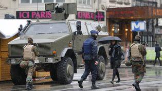 Des militaires et un policier belge patrouillant dans Bruxelles (Belgique), ville placée en état d'alerte maximale samedi 21 novembre. (YOUSSEF BOUDLAL / REUTERS)