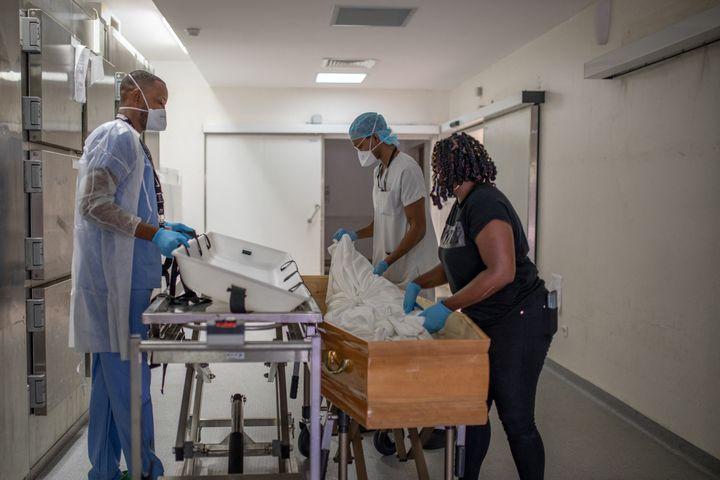 2 septembre 2021. Dans la morgue du CHU de Martinique, deux agents d'amphithéatre aident Chewyl, assistante funéraire, à déposer le corps d un patient décédé du Covid-19, dans un cercueil. (FANNY FONTAN / HANS LUCAS / AFP)