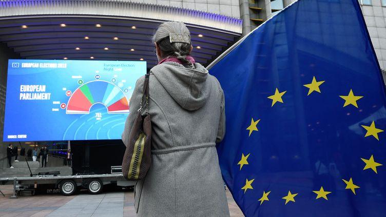 Une femme qui tient un drapeau européen en attendant les résultats des élections européennes devant le Parlement européen à Bruxelles. (JOHN THYS / AFP)