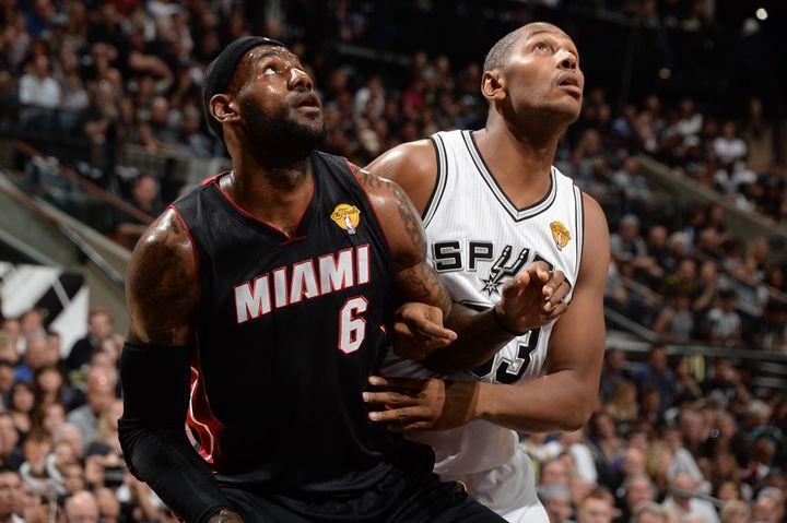 LeBron James à la lutte avecBoris Diaw (en maillot blanc), lors de la finale NBA, le 8 juin 2014, à San Antonio (Etats-Unis). (ANDREW D. BERNSTEIN / GETTY IMAGES / AFP)