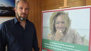Sébastien Chadaud-Pétronin, fils de Sophie Pétronin, à Bordeaux (Gironde) le 29 août 2018, devant une photo de sa mère, otage au Mali. (MEHDI FEDOUACH / AFP)