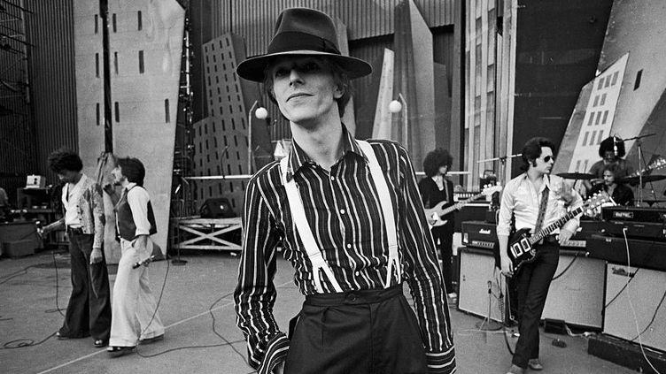 David Bowie à Los Angeles en septembre 1974, durant les répétitions de la seconde partie de son Diamond Dogs Tour, baptisé aussi The Soul/Philly/Dogs Tour. Le musicien Earl Slick est au second plan, 3e en partant de la droite.  (Terry o'Neill / Getty Images)