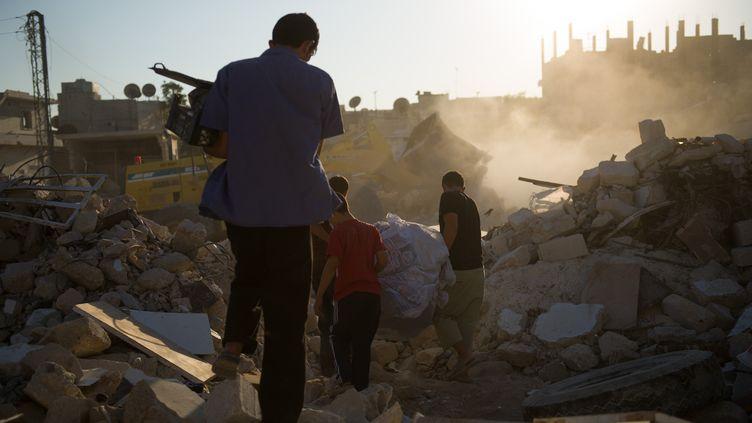 Des Syriens marchent sur les ruines de leur maison à Azaz, dans le nord du pays, le 19 août 2012. (PHIL MOORE / AFP)