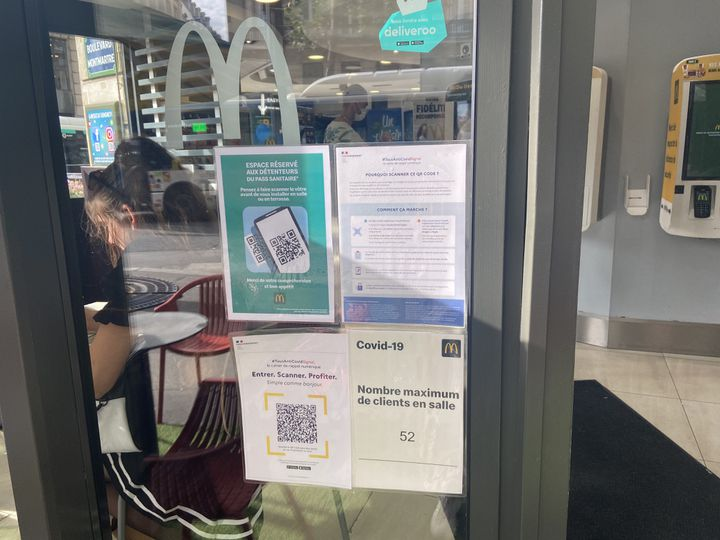 A l'entrée du McDonalds de Montmartre-Richelieu Drouot, dans le 9e arrondissement de Paris, des affiches rappellent les règles en vigueur concernant le pass sanitaire, le 10 août 2021. (RACHEL RODRIGUES / FRANCEINFO)