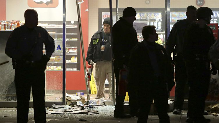 Des officiers de police devant l'entrée d'un commerce saccagé à Berkeley (Missouri), le 24 décembre 2014. (DAVID CARSON/AP/SIPA)