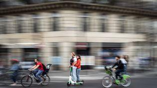 Des utilisateurs de trottinettes électriques au milieu de la circulation parisienne, le 13 septembre 2019. (MARTIN BUREAU / AFP)