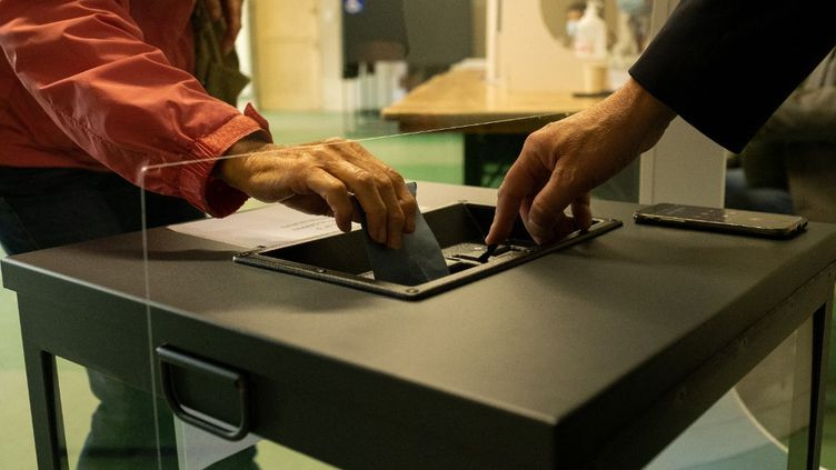 Un bulletin déposé dans une urne, au premier tour des élections régionales et départementales, le 20 juin 2021. (MARTIN BERTRAND / HANS LUCAS / AFP)