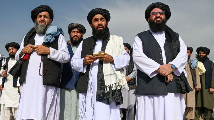 Le porte-parole des talibans, Zabihullah Mujahid (au centre), s'adresse aux médias à l'aéroport de Kaboul (Afghanistan), le 31 août 2021. (WAKIL KOHSAR / AFP)