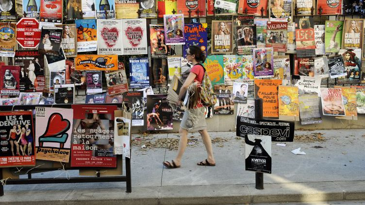 Une comédienne installe une affiche de son spectacle, le 5 juillet 2013 à Avignon (Vaucluse). (ANNE-CHRISTINE POUJOULAT / AFP)