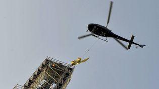 L'archange Saint-Michel est décroché avec l'aide d'un hélicoptère, le 15 mars 2016, au Mont-Saint-Michel (Manche). (MAXPPP)