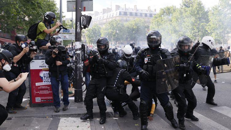 Des journalistes filment une arrestation par la police lors d'un rassemblement contre le racisme et les violences policières à Paris, le 13 juin 2020. (THOMAS SAMSON / AFP)