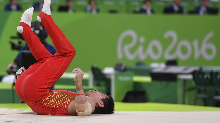 Le gymnaste chinois You Hao tombe des barres parallèles, le 16 août 2016, aux JO de Rio (Brésil). (BEN STANSALL / AFP)
