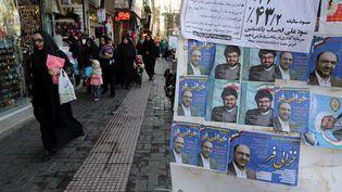 Des Iraniens passent devant des affiches électorales, le 24 février 2016, à Qom (Iran). (ATTA KENARE / AFP)