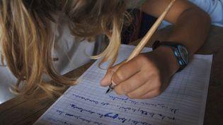 Une élève de CM2 écrit une dictée dans une école primaire de Caen (Calvados), le 8 juin 2007. (MYCHELE DANIAU / AFP)