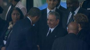 Barack Obama et Raul Castro se saluent, le 10 décembre 2013, à Soweto (Afrique du Sud). (  FRANCETV INFO )