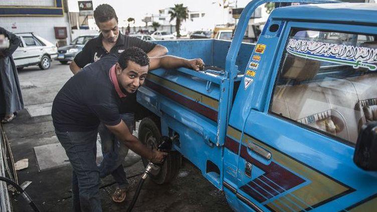 Le geste qui coûte cher en Egypte aujourd'hui. Le gouvernement réduit les subventions sur les carburants. Résultat, les prix s'envolent. (KHALED DESOUKI / AFP)