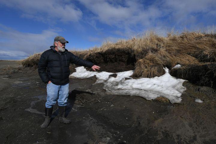 L'archéologue Rick Knecht montre les effets du réchauffement climatique sur le site de fouilles où il recherche des objets de peuples anciens yupik, près de Quinhagak, en Alaska (12 avril 2019) (MARK RALSTON / AFP)