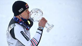 Alexis Pinturault embrasse le gros globe de Cristal, trophée pour le vainqueur du classement général de la Coupe du monde de ski alpin, le 20 mars 2021. (FABRICE COFFRINI / AFP)