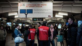 """Des """"gilets rouges"""" de la SNCF conseillent des voyageurs en gare de Lyon Part-Dieu, mardi 2 avril. (JEFF PACHOUD / AFP)"""
