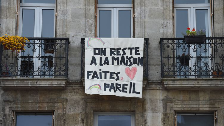 Des habitants de Bordeaux (Gironde) ont affiché une banderole sur leur balcon à destination de la population pour lutter contre le coronavirus, le 16 mars 2020. (NICOLAS TUCAT / AFP)