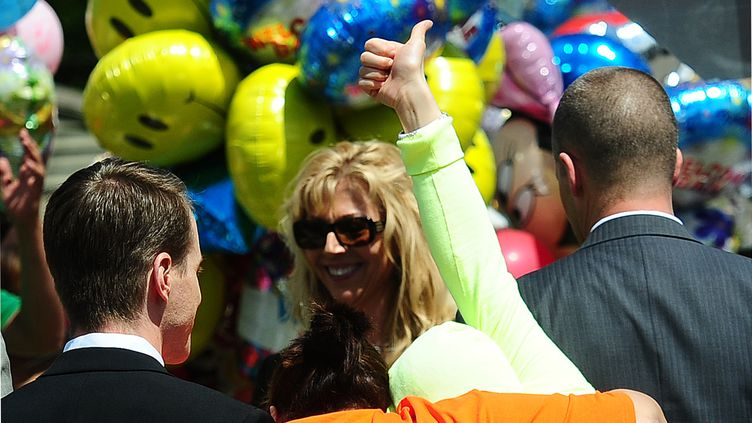 Gina DeJesus lève son pouce à son arrivée devant la maison familiale, le 8 mai 2013 à Cleveland, dans l'Ohio (Etats-Unis). (EMMANUEL DUNAND / AFP)